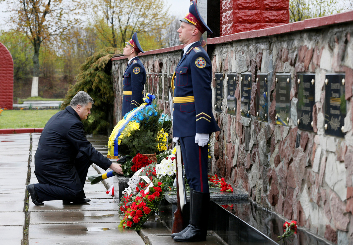 "Ukrainian President Petro Poroshenko lays flowers during a commemoration ceremony at a monument to ""liquidators"", emergency workers who fought the blaze at the Chernobyl nuclear reactor, near the Chernobyl nuclear power plant, Ukraine, April 26, 2016. REUTERS/Valentyn Ogirenko"